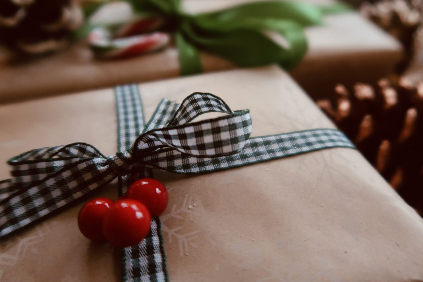 Brown wrapping paper with green chequered ribbon and red berries
